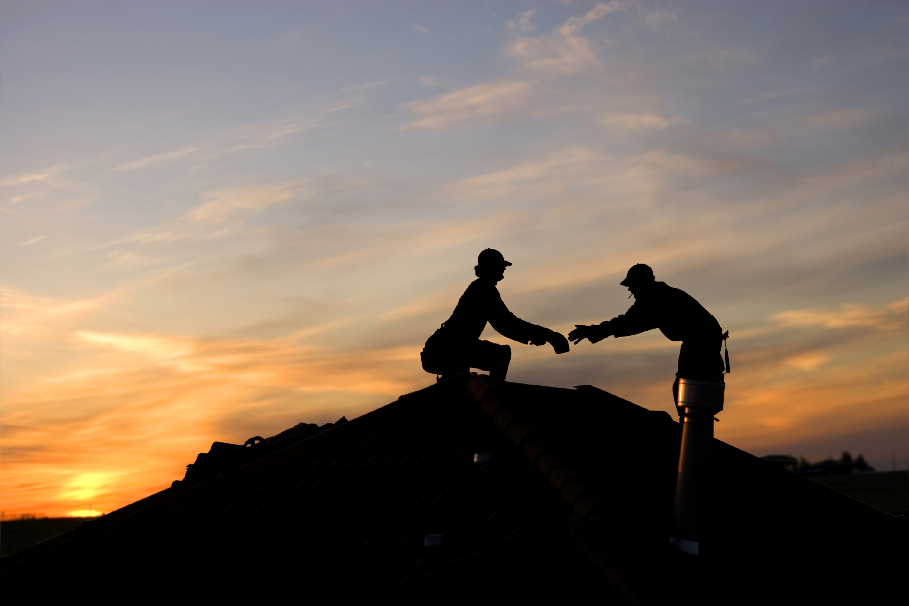 Two roofers working at dusk